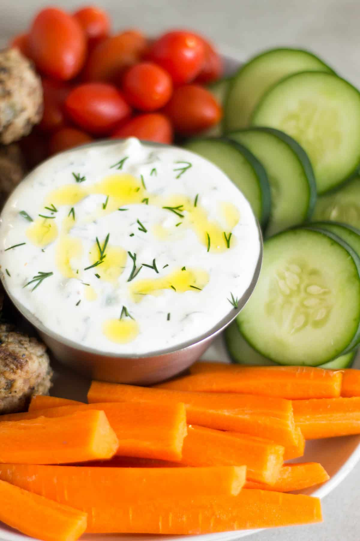 Close up of a bowl of tzatziki sauce with fresh raw veggies around it