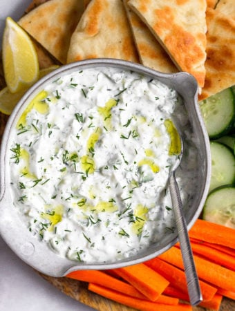 Bowl of homemade tzatziki topped with fresh dill and olive oil with a spoon coming out of it. Around it is sliced carrots, cucumbers, and peta bread with two lemon wedges.