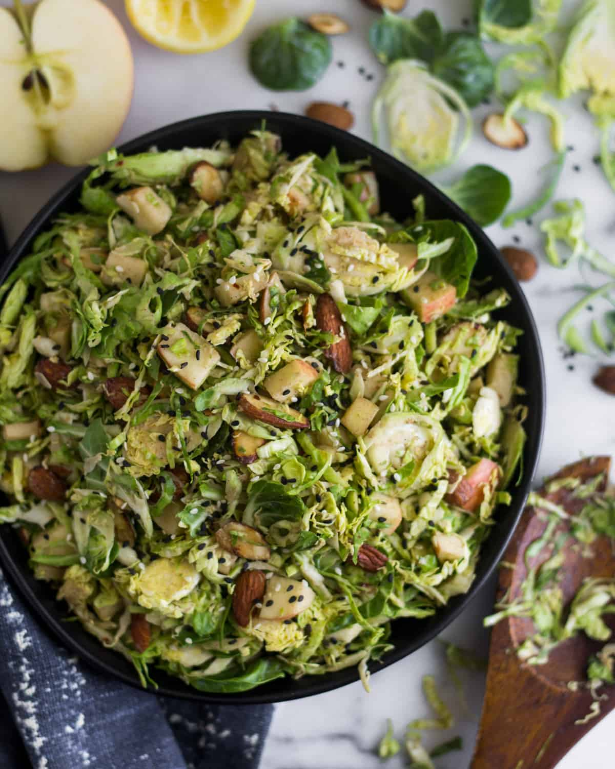 Big bowl with apple & shaved brussels sprouts salad surrounded by half an apple, half a lemon, brussels sprouts leaves, and almonds
