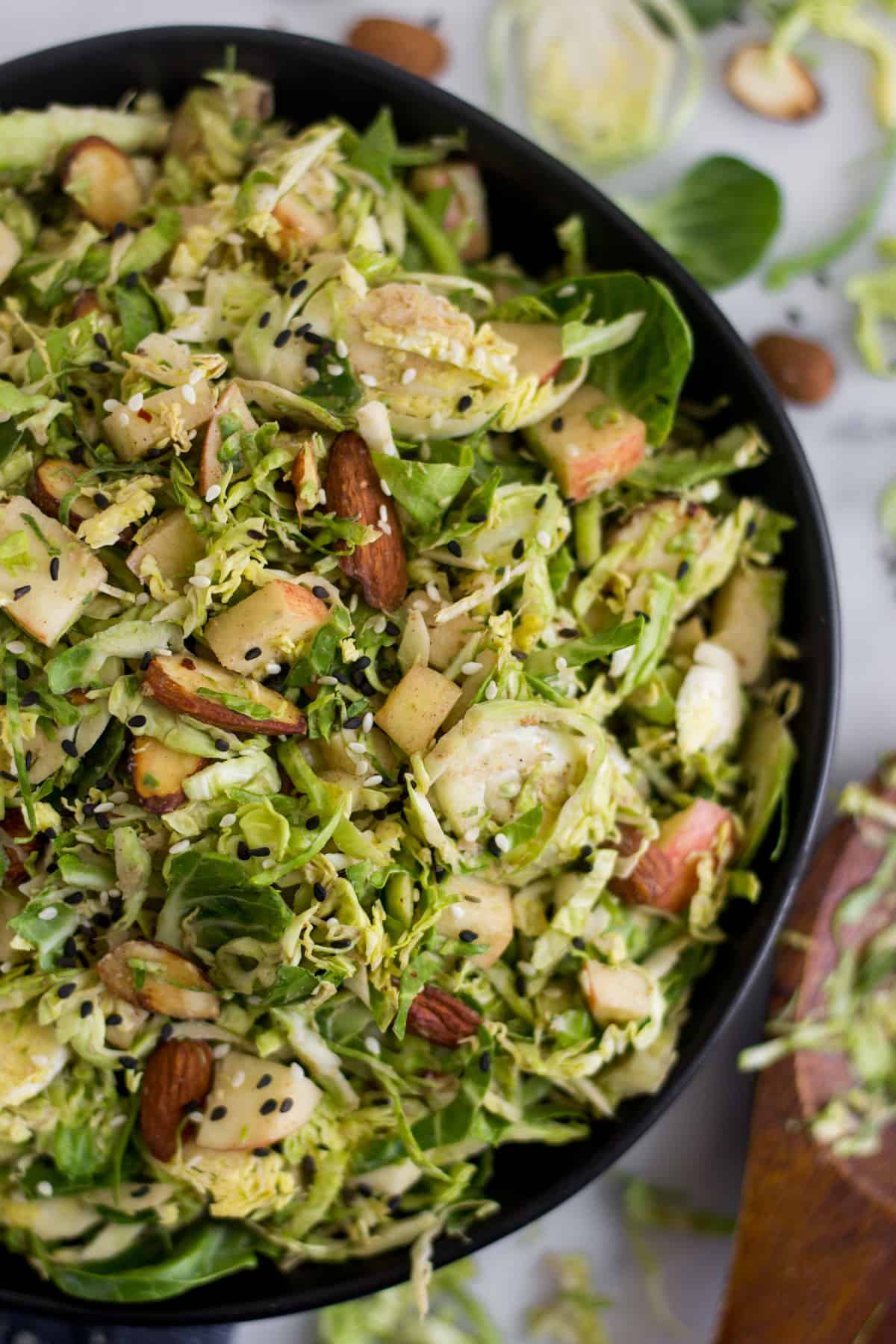 Close up of a black bowl with apple & shaved brussels sprouts salad