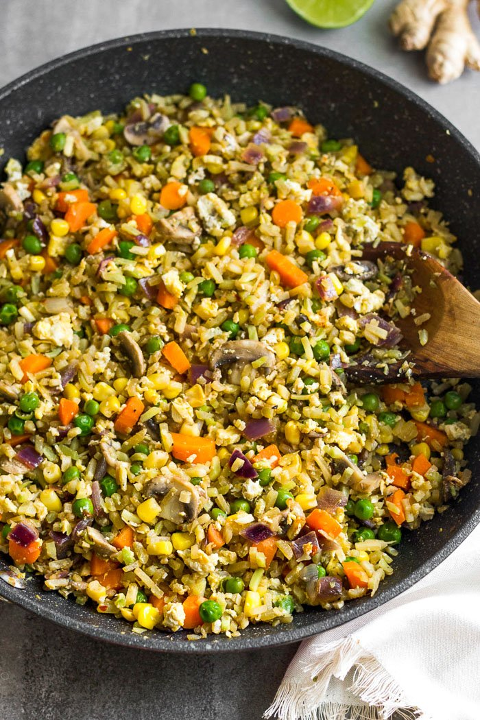 Large pan filled with riced broccoli fried rice.