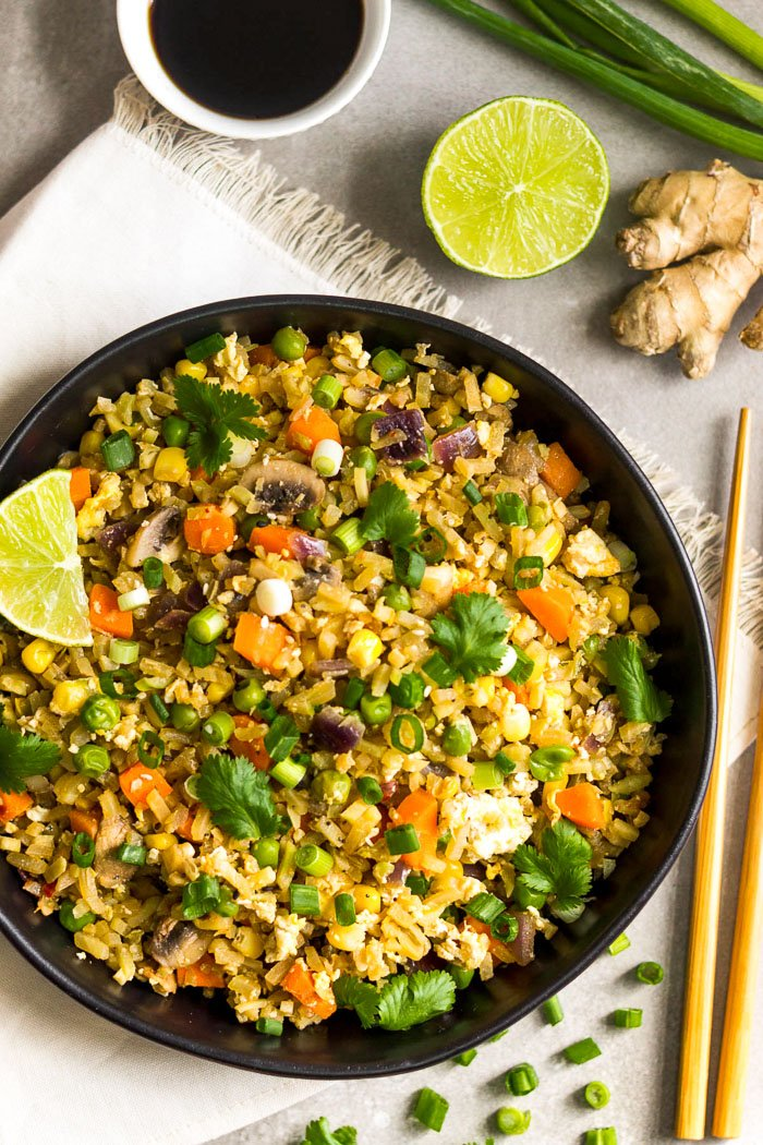 Overhead shot of a large black bowl filled with veggies fried rice topped with cilantro and a lime wedge. Around it is chopsticks, half a lime, ginger, bowl of coconut aminos, and green onions.