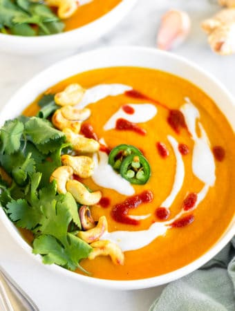 Bowl of curried butternut squash soup topped with coconut milk, hot sauce, sliced jalapenos, cashews, and cilantro. Behind it is another bowl and a clove of garlic and fresh ginger.