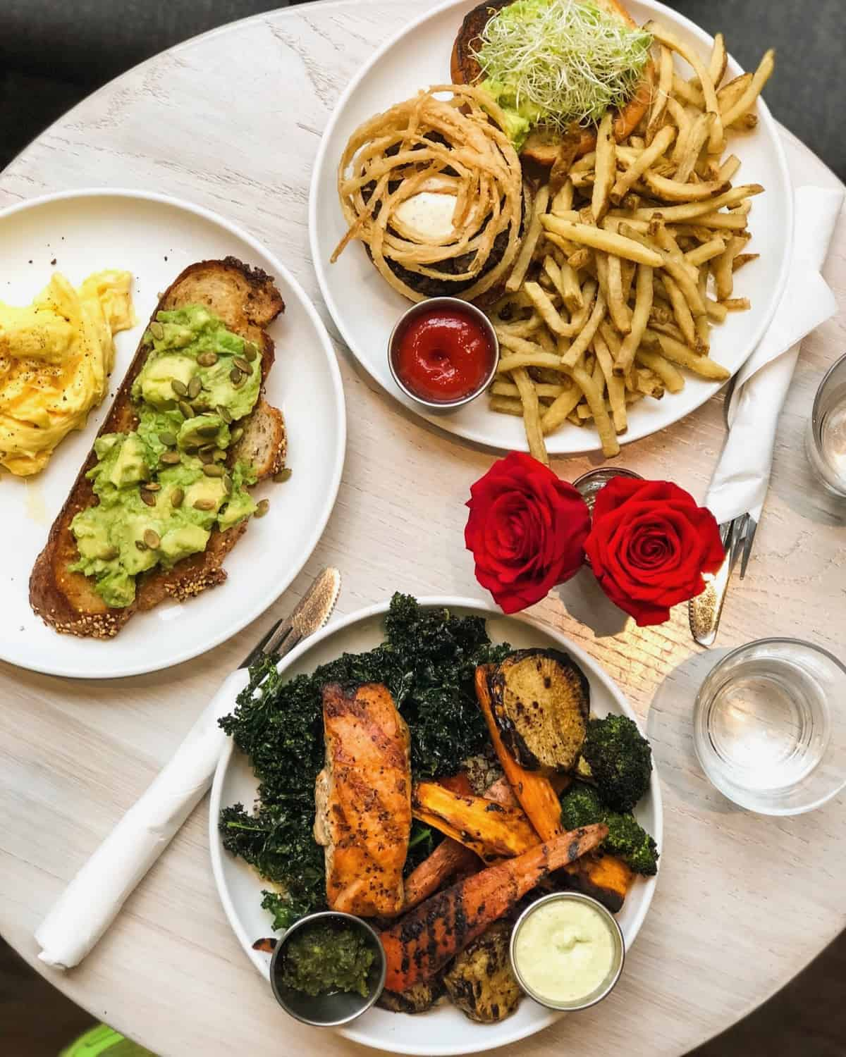 Table of a big bowl of veggies with grilled salmon on it, avocado toast with scrambled eggs, and a veggie burger with french fries
