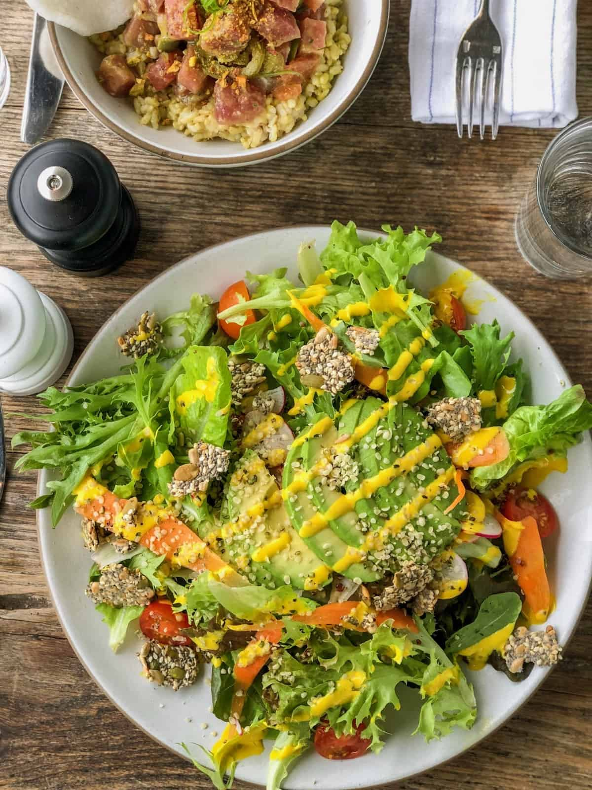 Salad topped with fresh veggies, avocado, and a turmeric tahini dressing