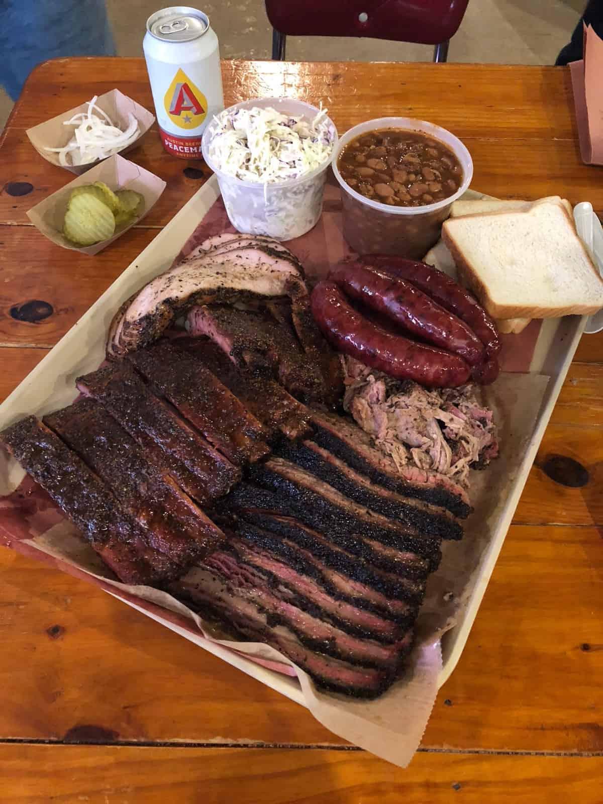 Huge pile of BBQ on a baking sheet - brisket, pulled pork, sausage, beans, coleslaw, turkey, and ribs,
