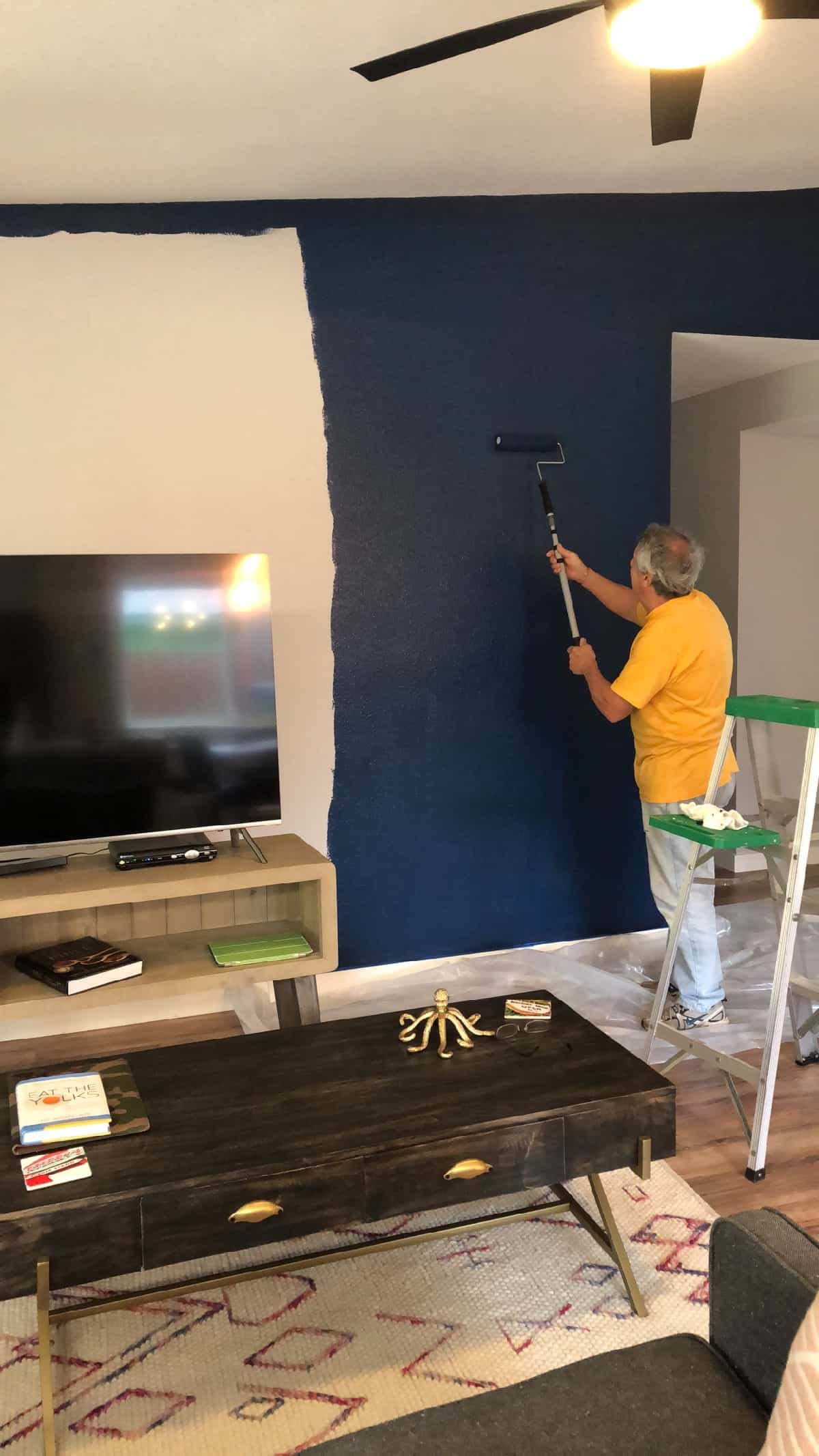 A guy painting a wall dark blue in a living room