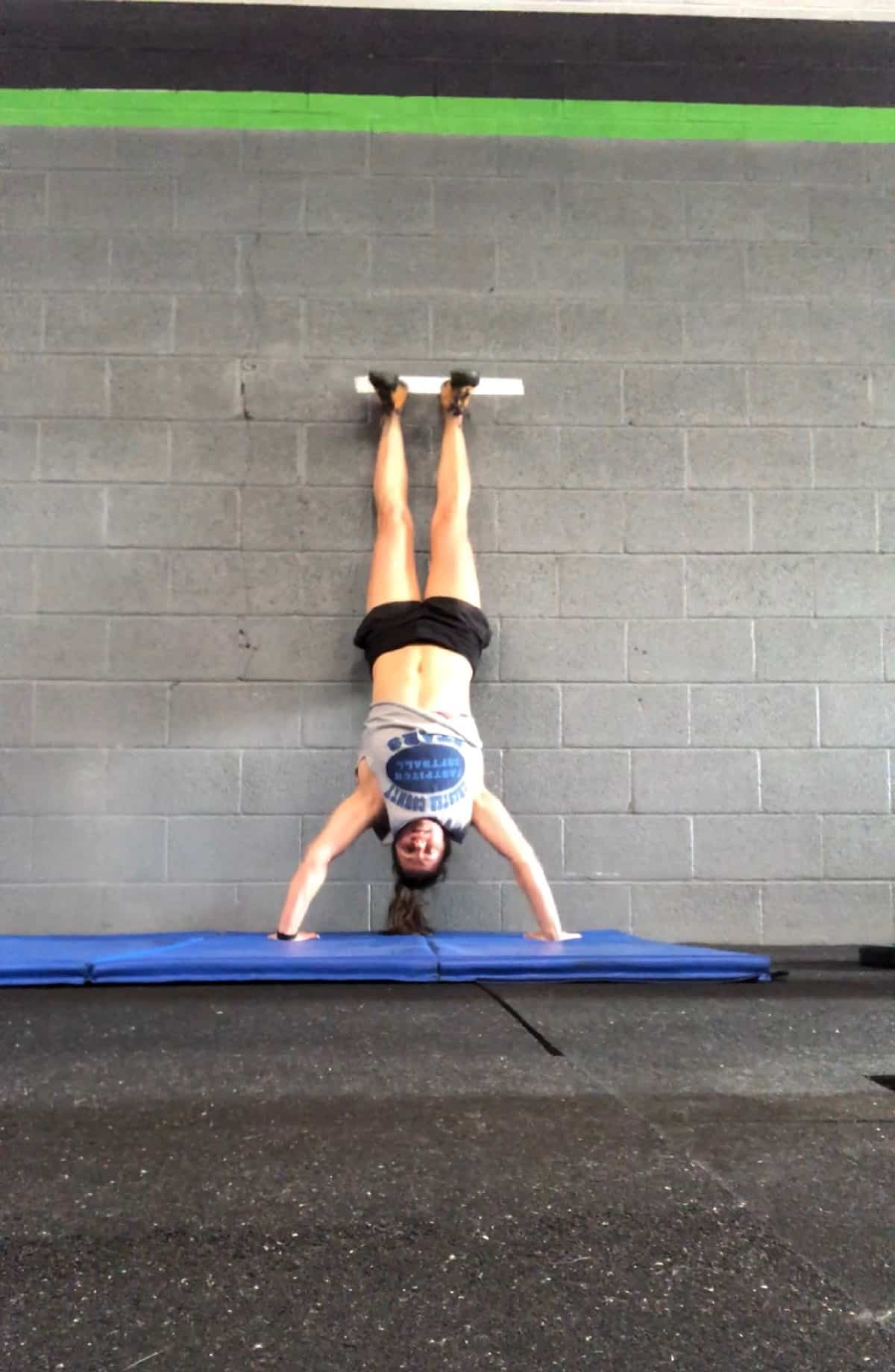 Girl upside-down against a wall doing a handstand push-up