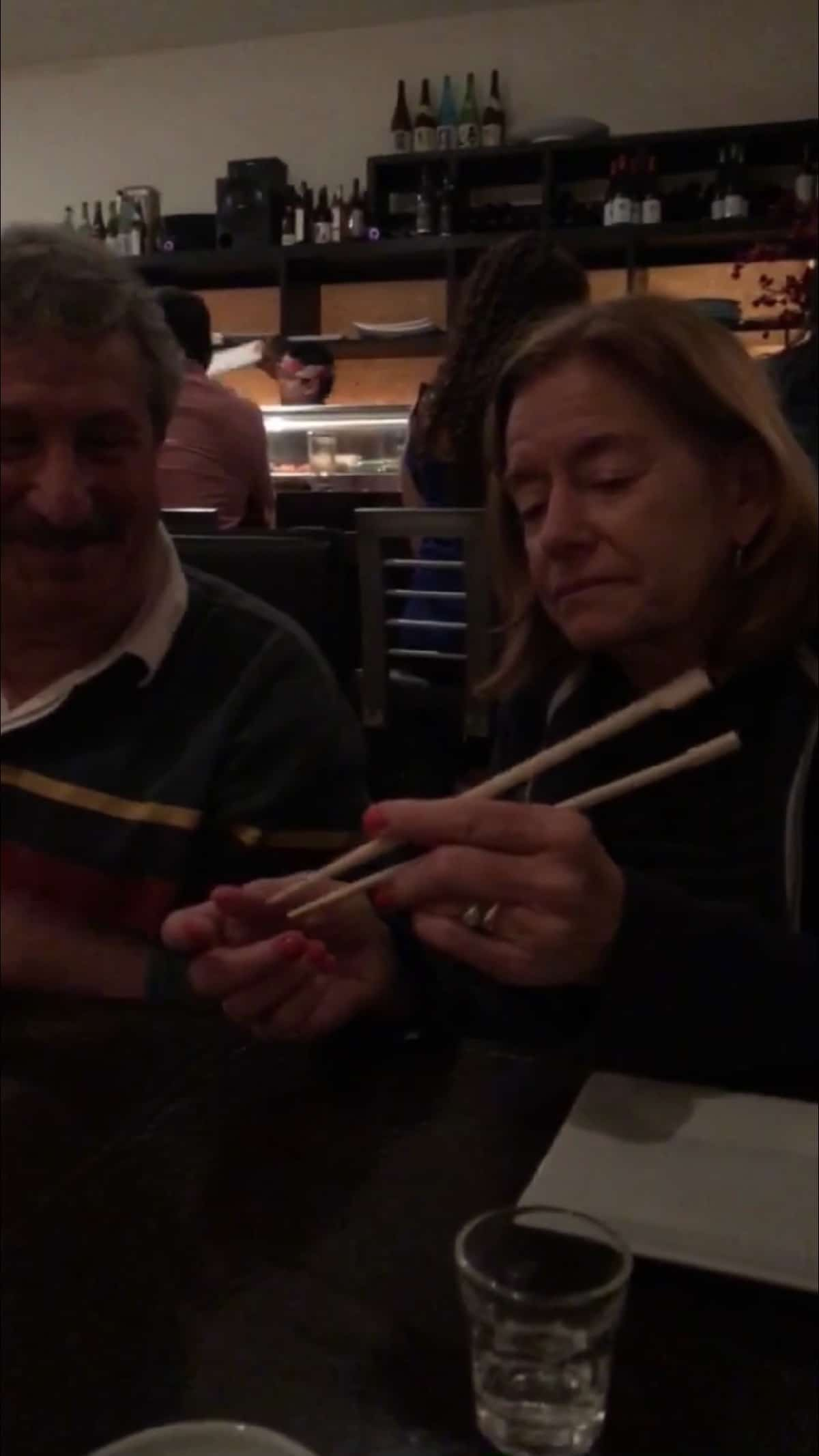 Lady showing a man how to use chopsticks