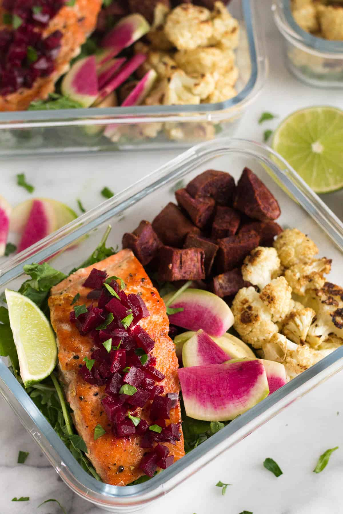 Two meal prep containers of greens, roasted veggies, and pan friend salmon topped with beets and a lime wedge.