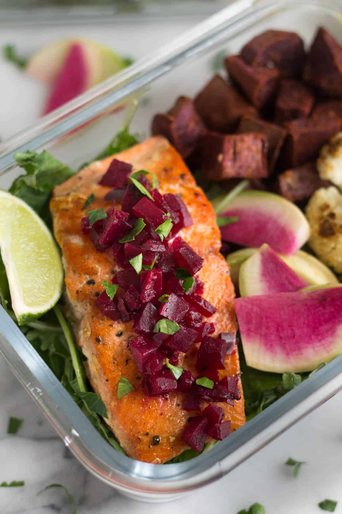Close up of pan friend salmon topped with chopped beets and other veggies in a glass container