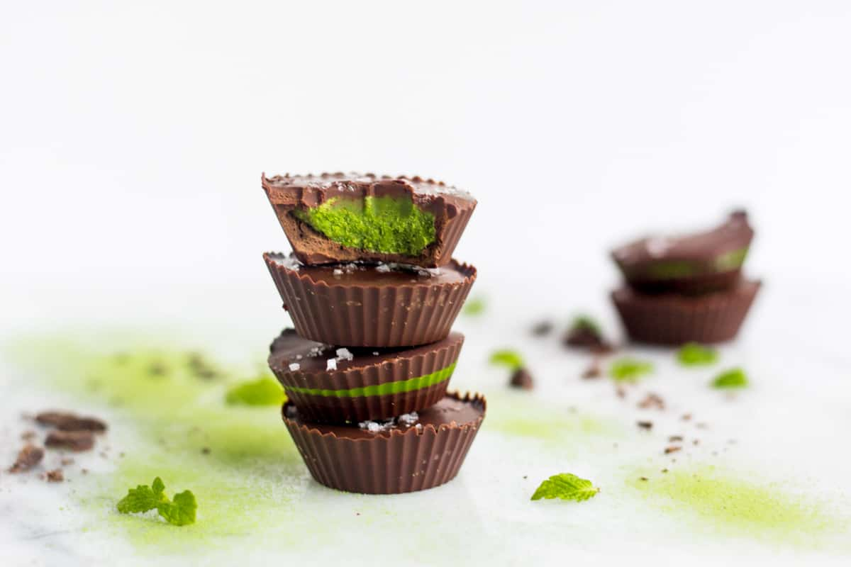 A stack of 4 Collagen Mint Matcha Coconut Butter Cups surrounded with chocolate and mint leaves with 2 in the background