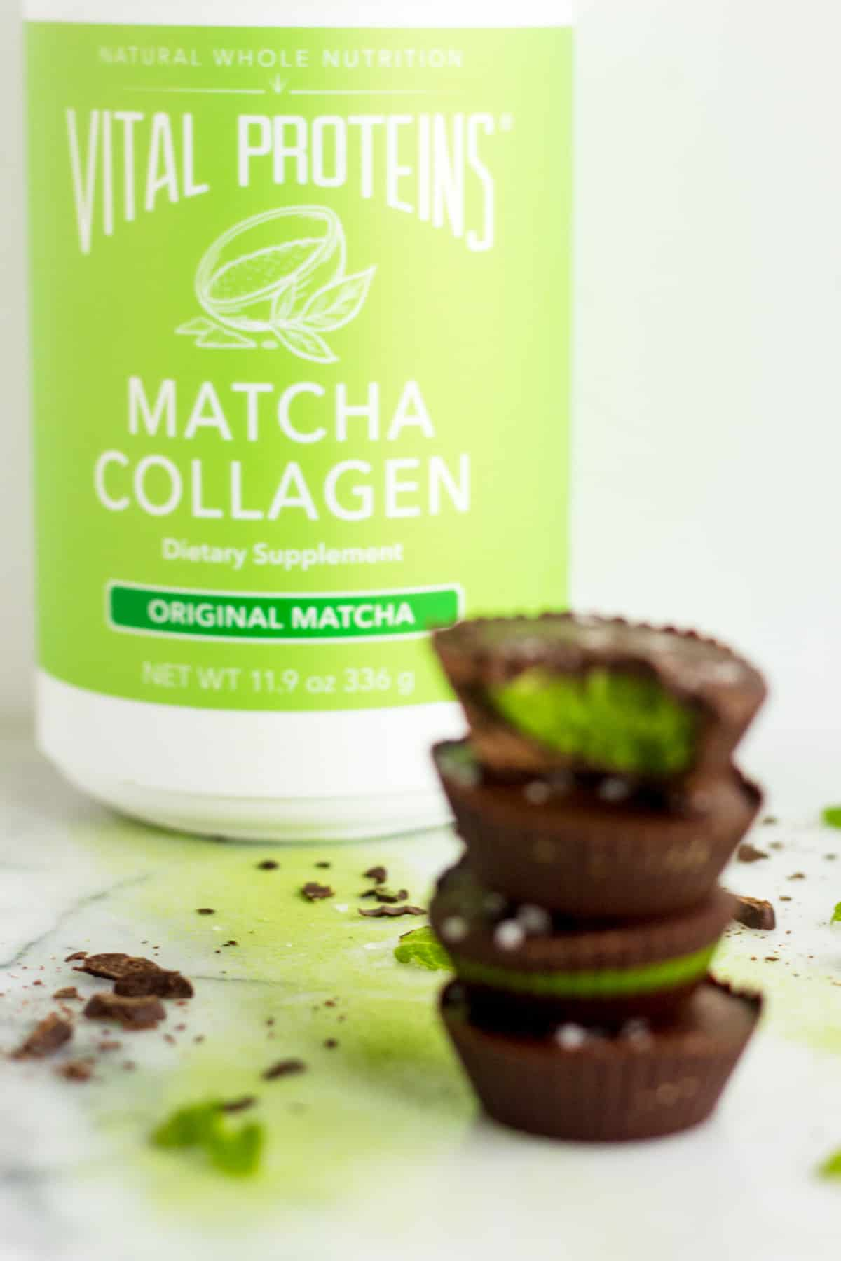 4 Collagen Mint Matcha Coconut Butter Cups stacked on drop of each other with a container of Vital Proteins Matcha Collagen in the background in focus