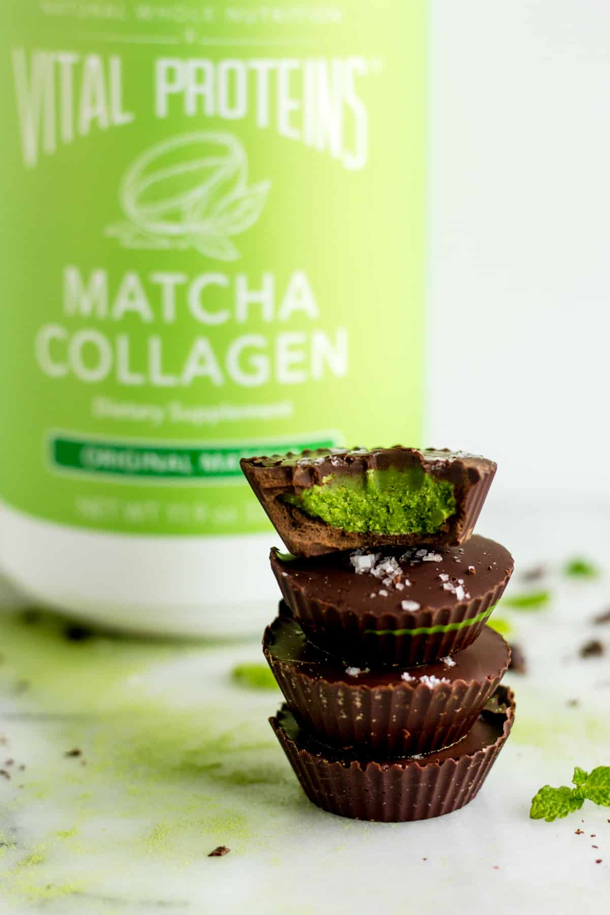A stack of 4 Collagen Mint Matcha Coconut Butter Cups with a container of Vital Proteins Matcha Collagen in the background