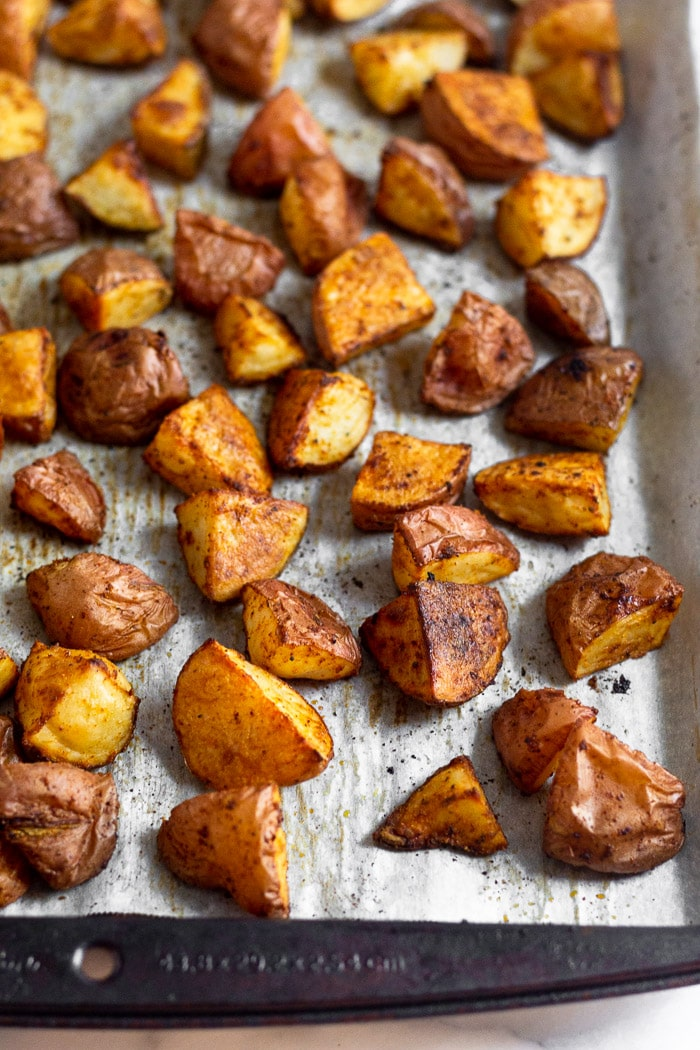 Sheet pan filled with roasted red potatoes.