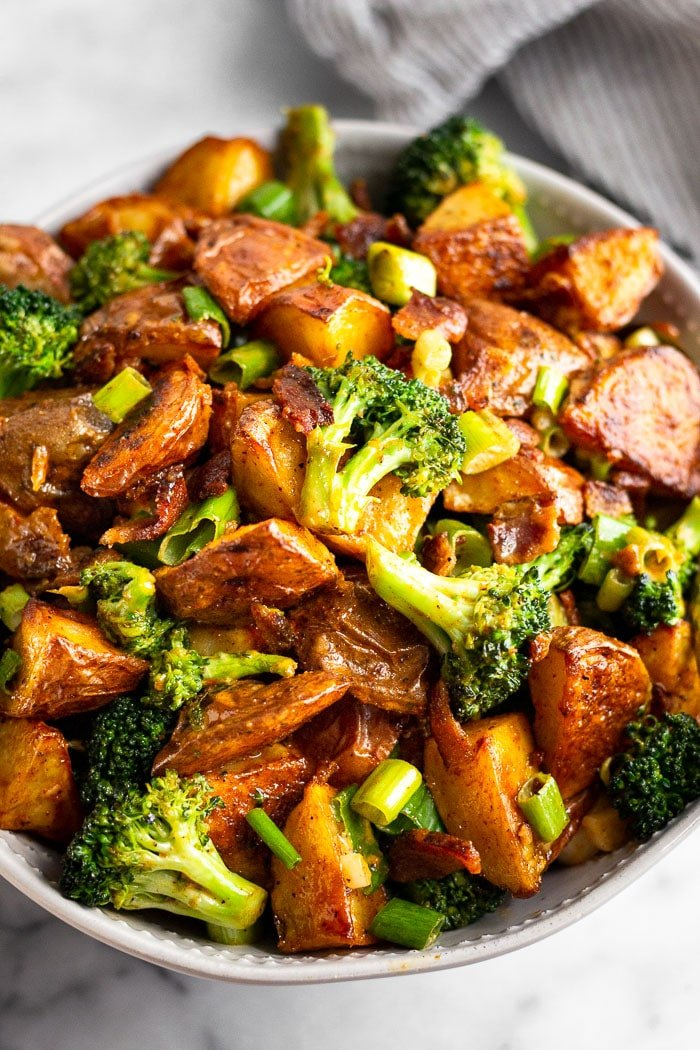 Close up of roasted red potato salad with broccoli and bacon in a large white bowl.