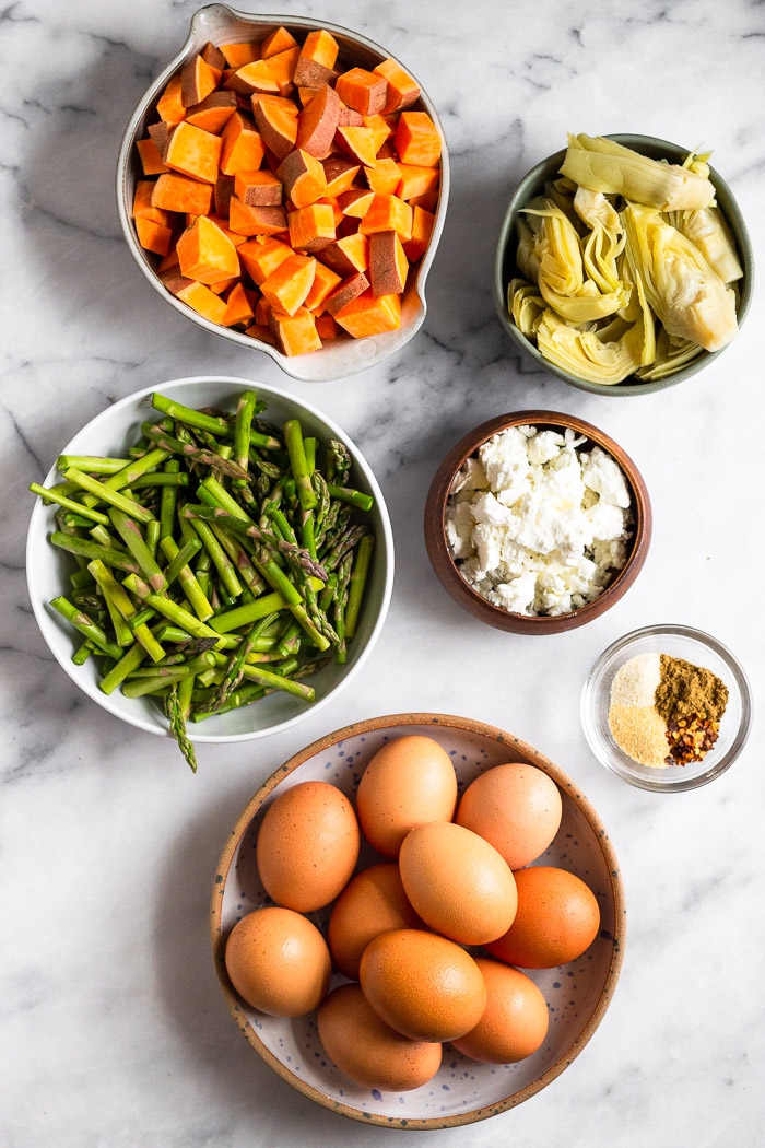 Overhead shot of a bowl of diced sweet potatoes, bowl of artichoke hearts, bowl of goat cheese, small bowl of spices, bowl of eggs, and a bowl of asparagus.