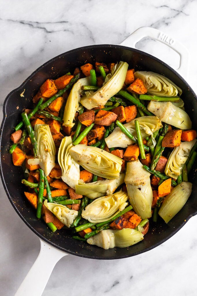 Pan filled with sautéed sweet potatoes, asparagus, and artichoke hearts.