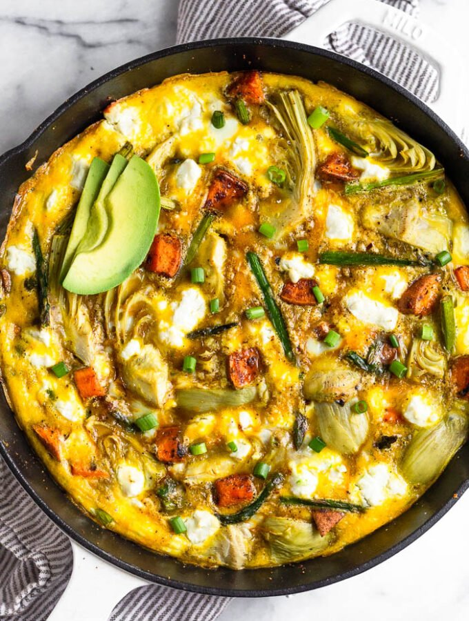 Overhead shot of a sweet potato frittata with asparagus topped with avocado and green onions.