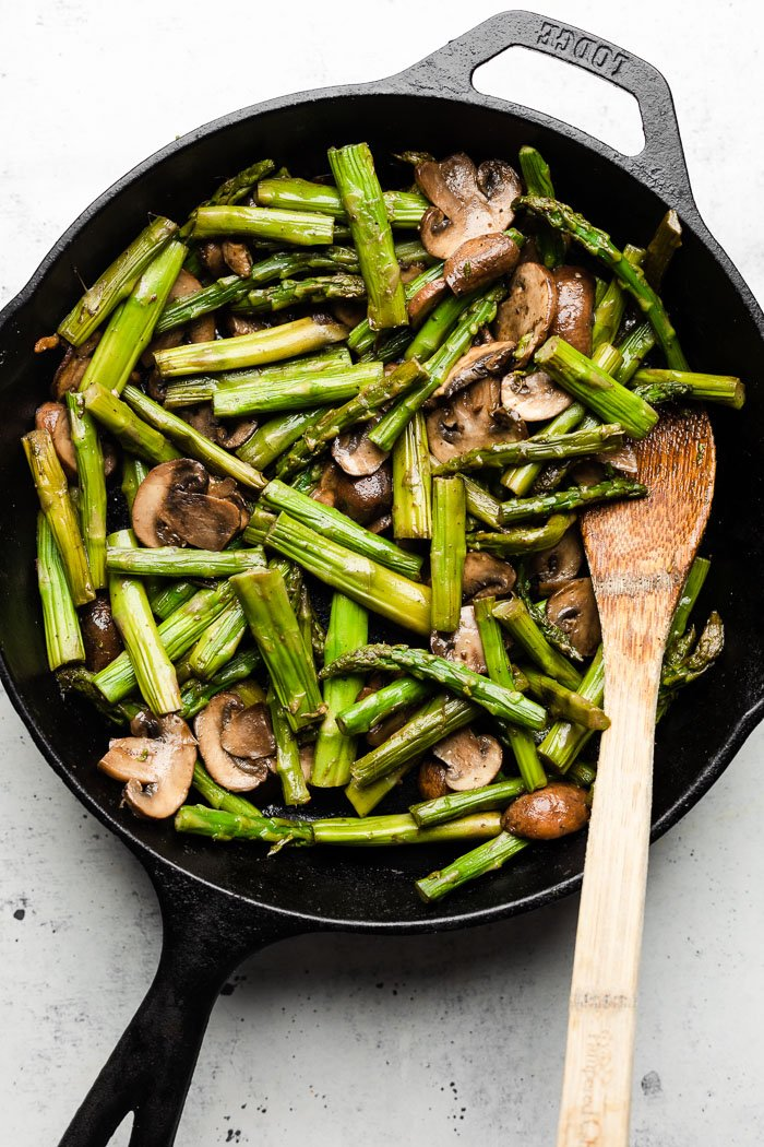 Sautéed asparagus and mushrooms in a skillet with a wooden spoon in it.