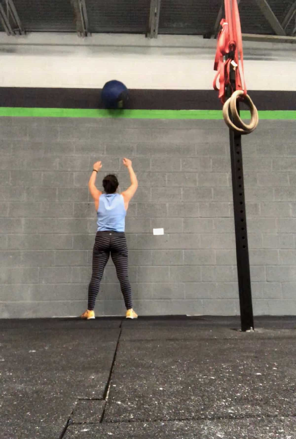 Girl throwing a med ball in the air against the wall doing a wall ball