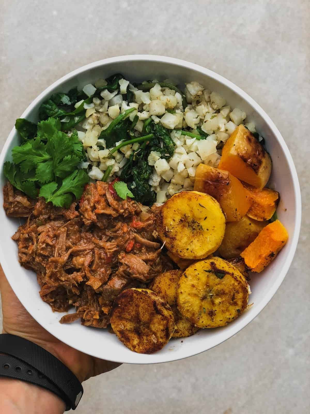 Bowl of ropa vieja with cauliflower rice, roasted butternut squash, and sautéed plantains
