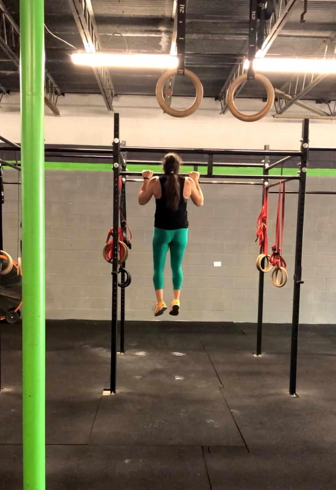Girl in green leggings doing a strict pull-up