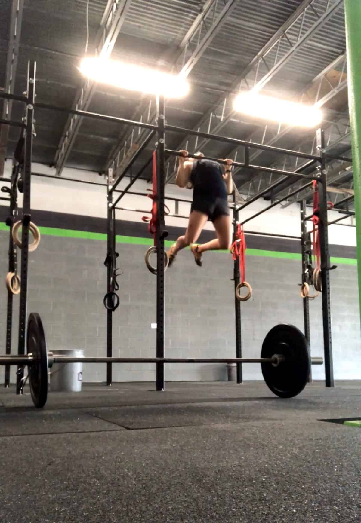 Girl doing a chest to bar pull-up