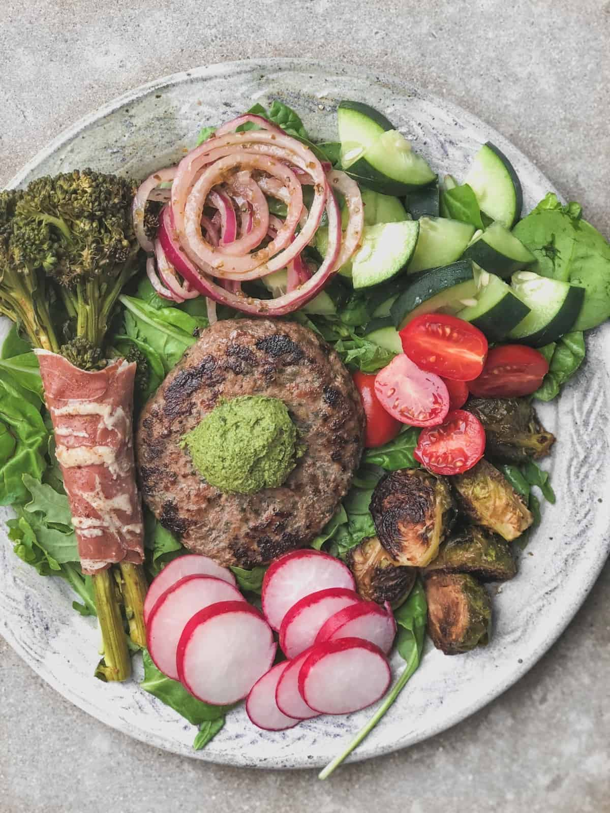 Big plate with greens, broccolini wrapped with prosuitto, marinated onions, cucumbers, tomatoes, brussels sprouts, radishes, and a burger with pesto on top