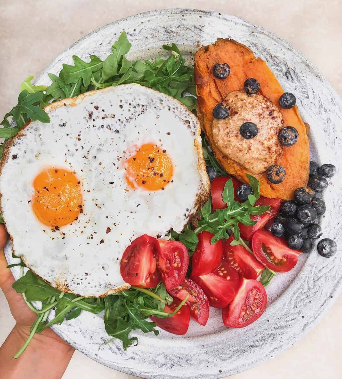 Plate with two fried eggs, half a sweet potato with almond butter and blueberries on it, and tomatoes all over greens