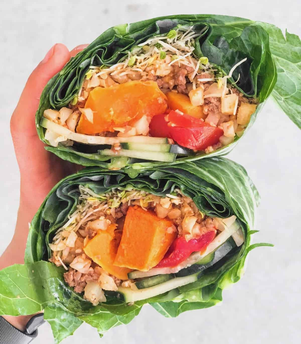Collard wrap filled with ground beef, cauliflower rice, butternut squash, tomatoes, cucumber, and sprouts