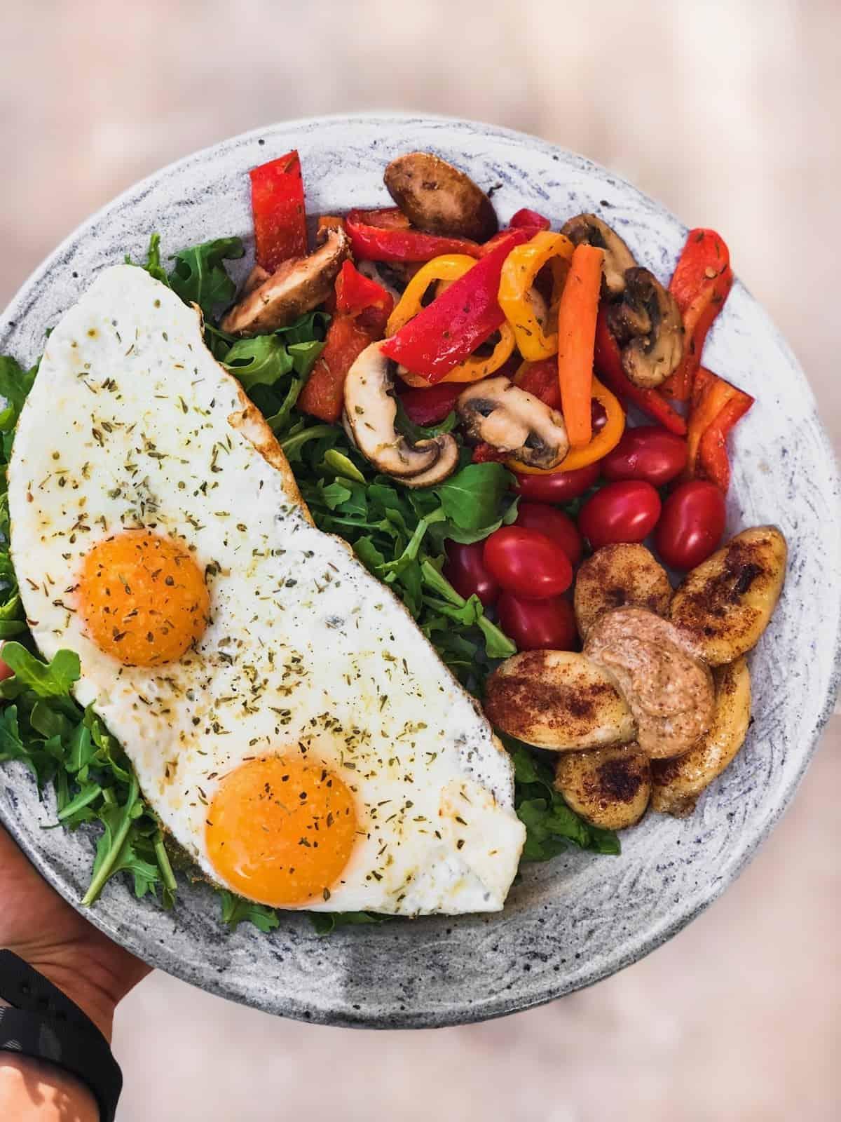 Plate of greens, 2 fried eggs, sautéed veggies, and a sautéed banana with almond butter