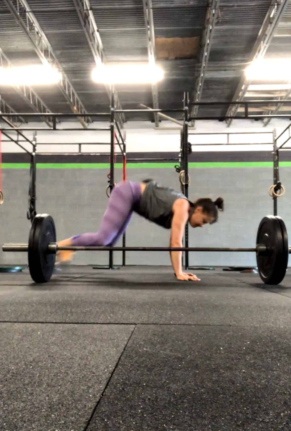 Girl doing a lateral burpee over a barbell