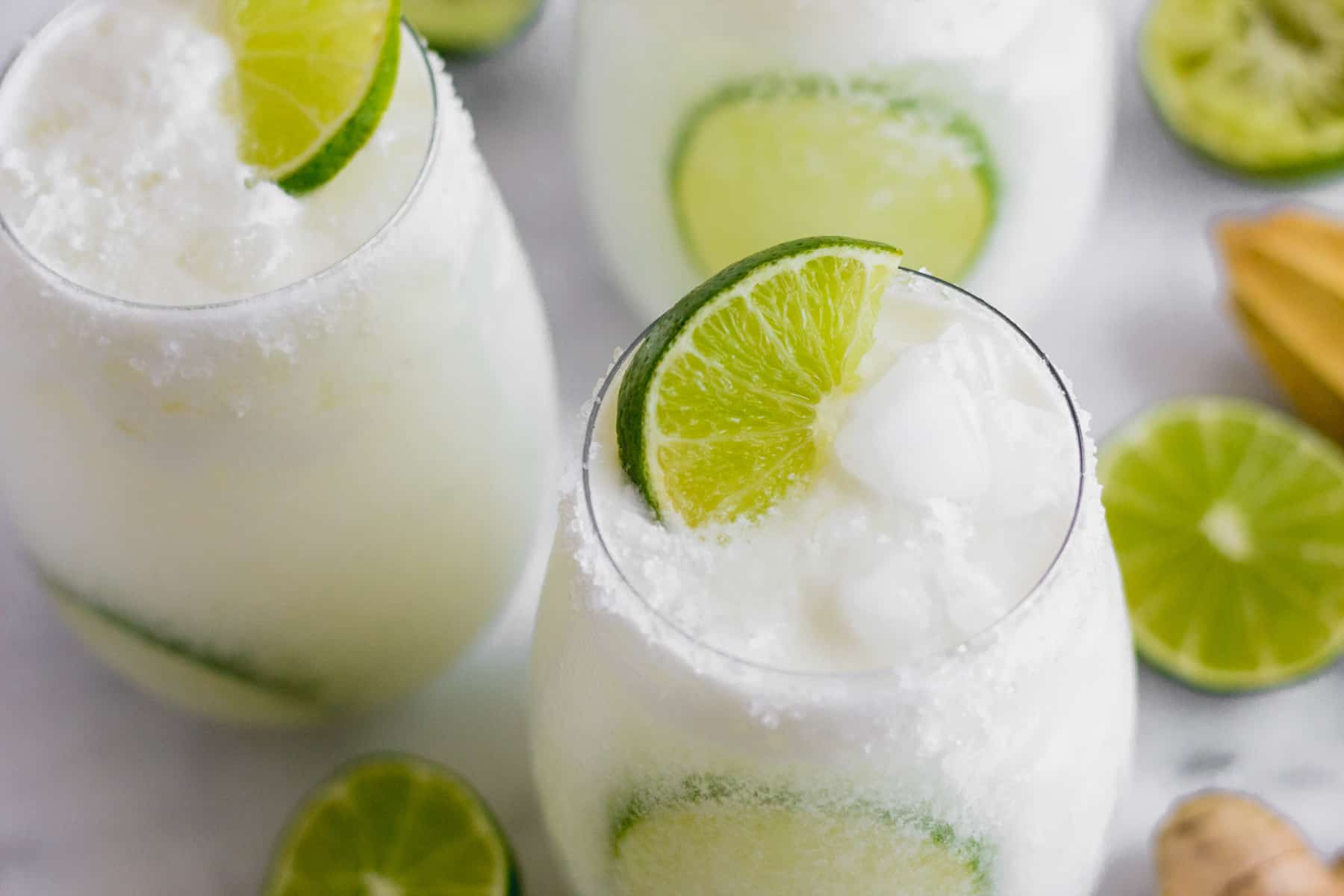 Three glasses filled with coconut lime mocktail on a white countertop surrounded by limes