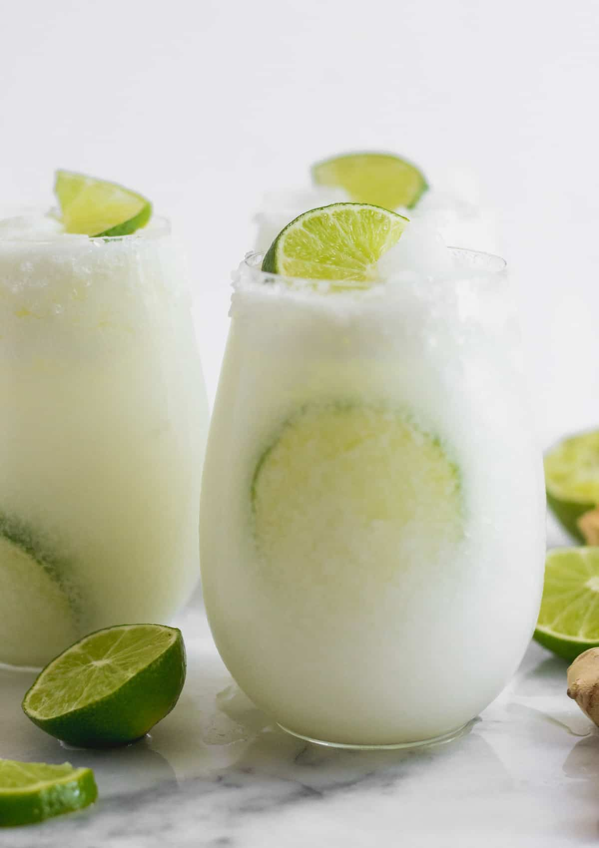 Glass filled with coconut lime mocktail with a lime in the glass and garnished with a lime wedge