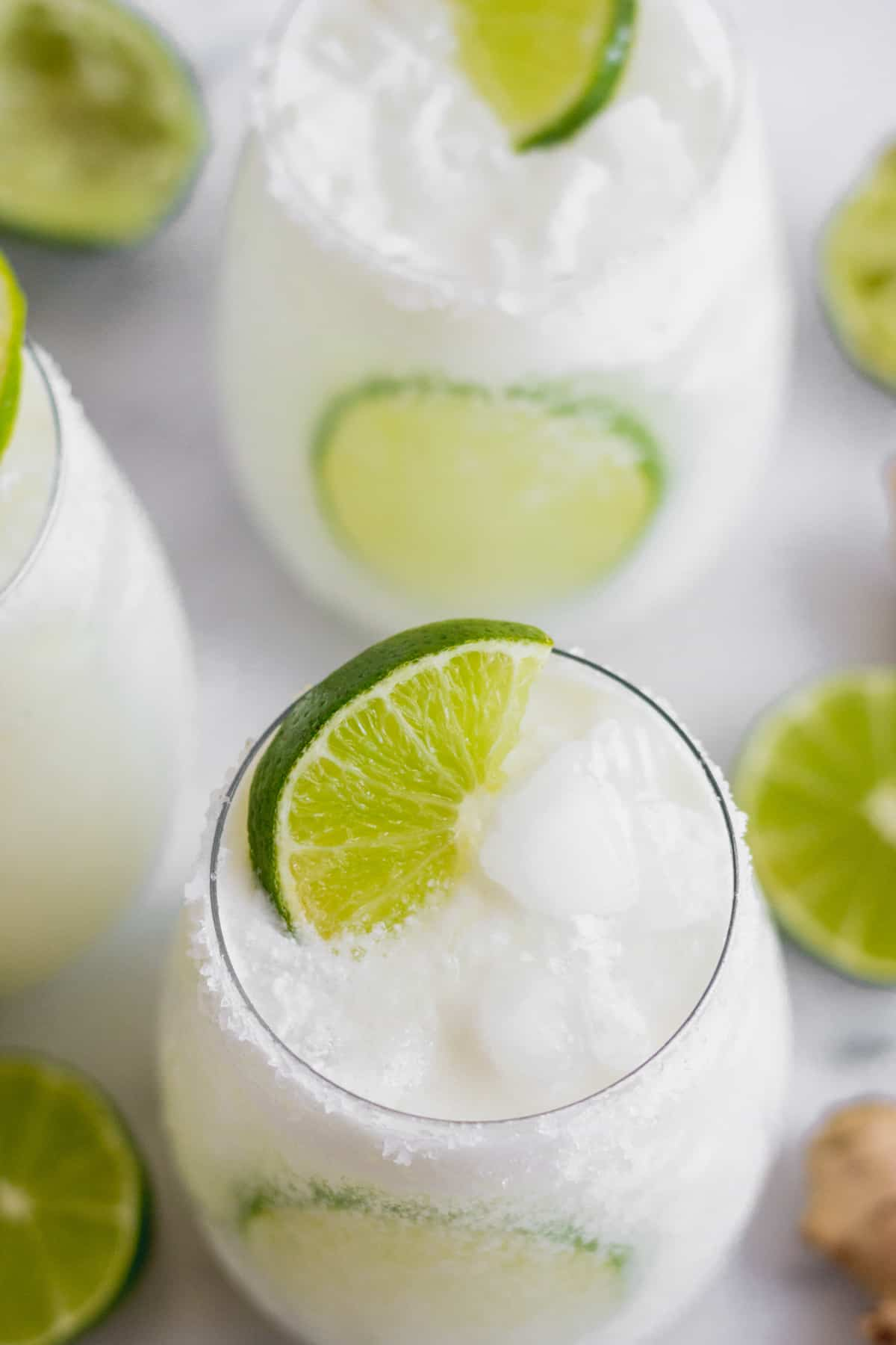 Overhead shot of 2 glasses filled with a coconut mocktail garnished with limes