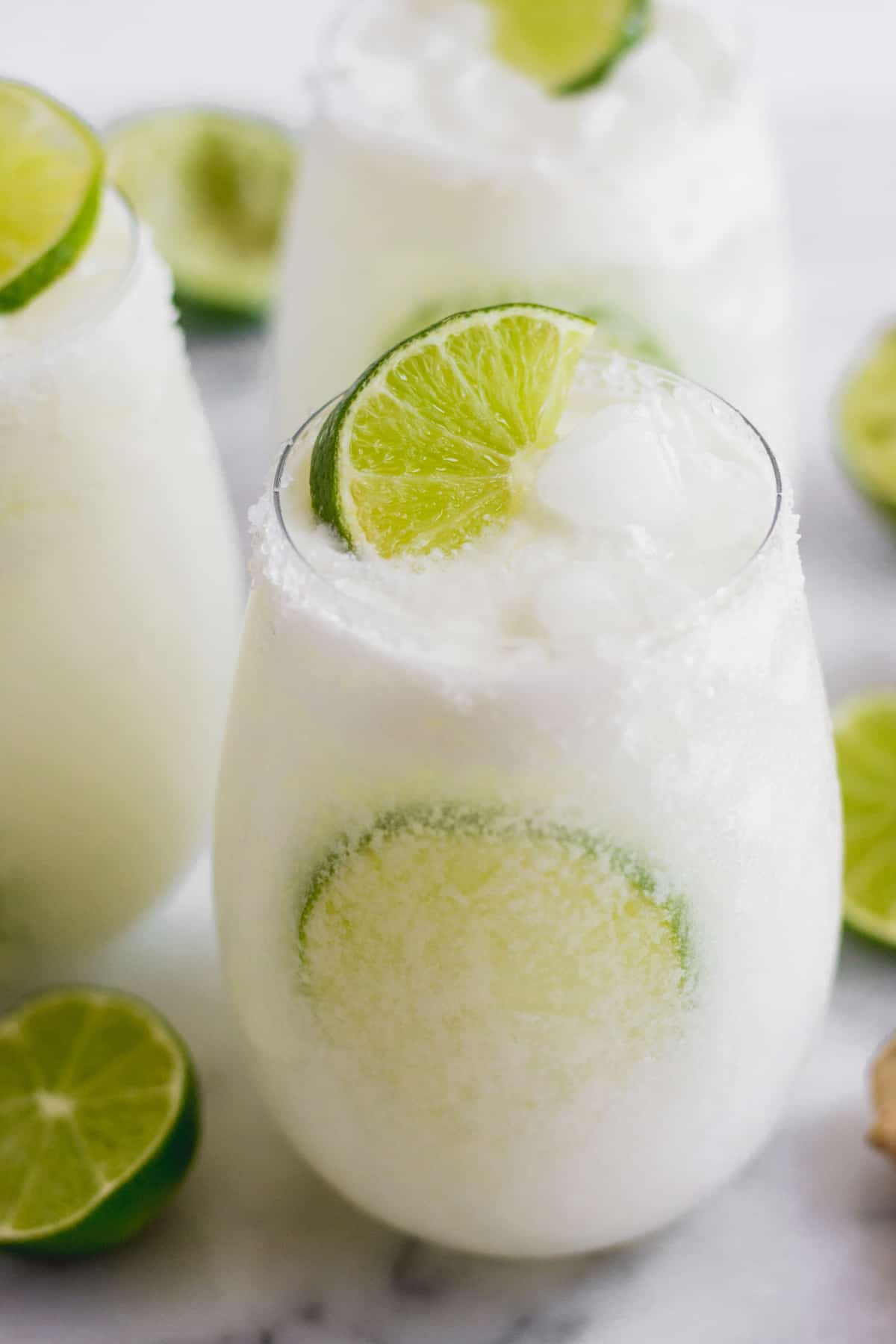 Glass with a salted rim filled with a coconut mocktail and limes