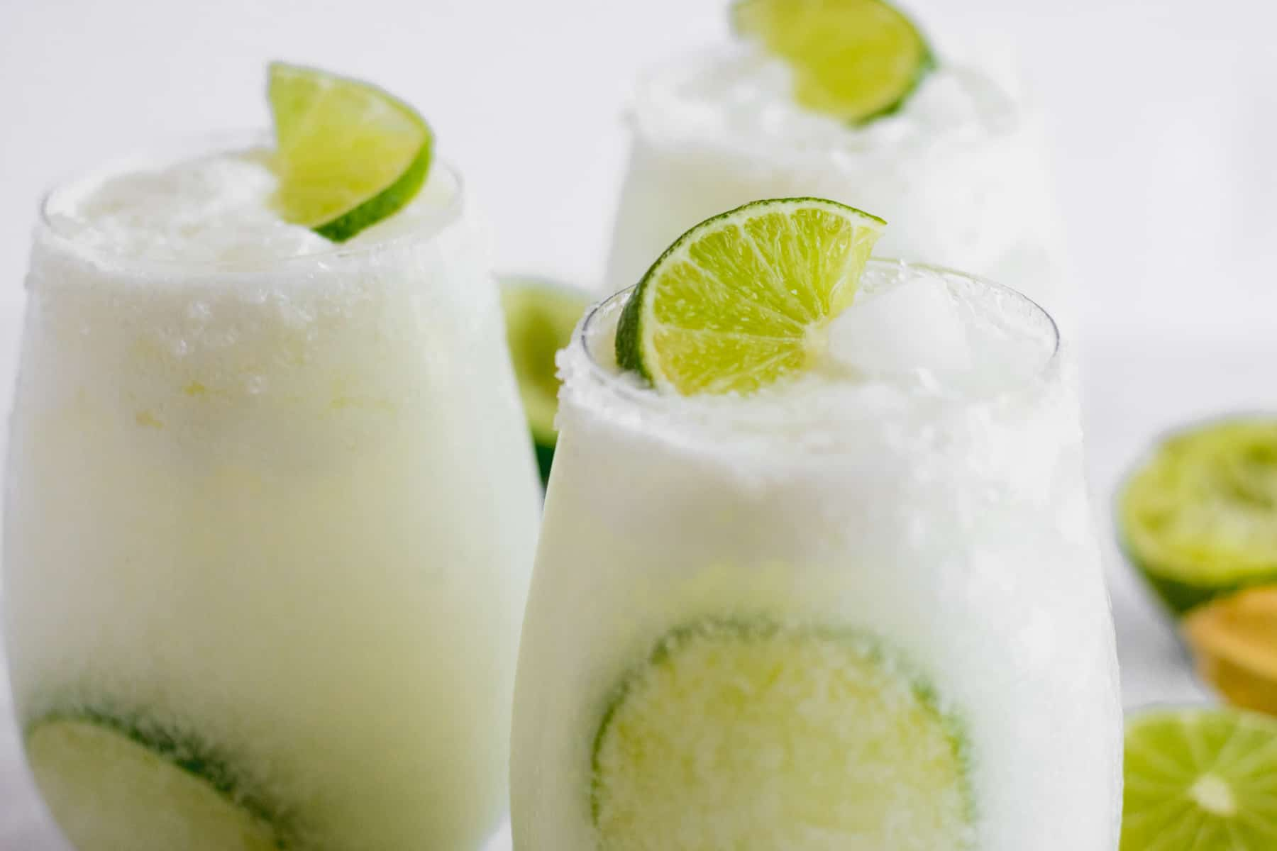 Three glasses filled with coconut lime mocktail garnished with lime wedges
