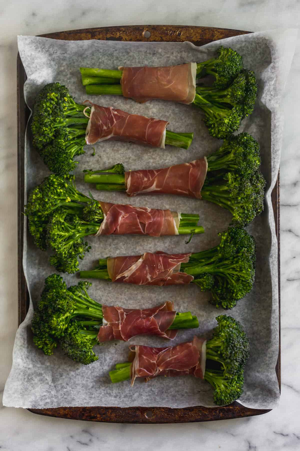 Pan of broccolini wrapped in prosciutto before it will be baked in the oven