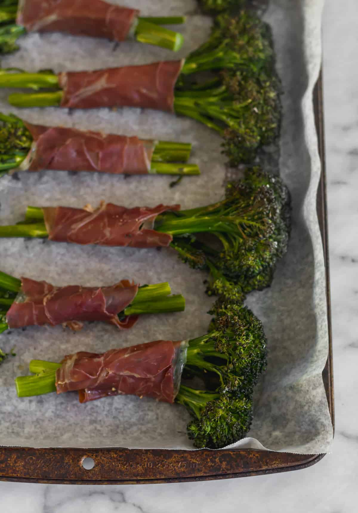Pan of baked broccolini wrapped in crispy prosciutto after it was roasted in the oven