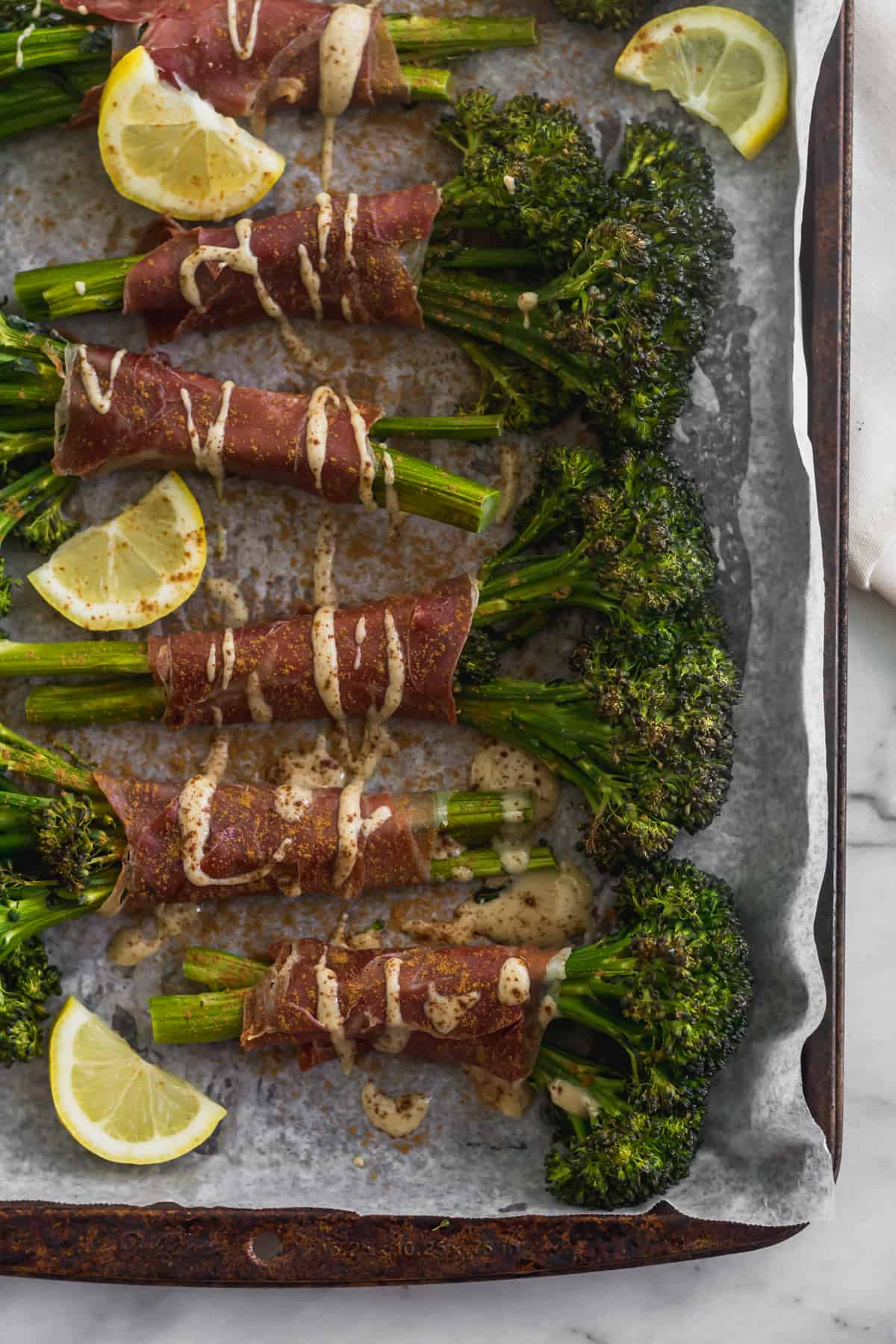 Sheet pan with a bunch of prosciutto wrapped broccolini surrounded by lemon wedges and drizzled with tahini and cinnamon