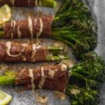 Roasted Broccolini wrapped in prosciutto on a sheet pan drizzled with tahini, lemon juice, and cinnamon