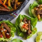 Cast iron pan filled with steak fajitas and avocado surrounded by steak fajita lettuce wraps
