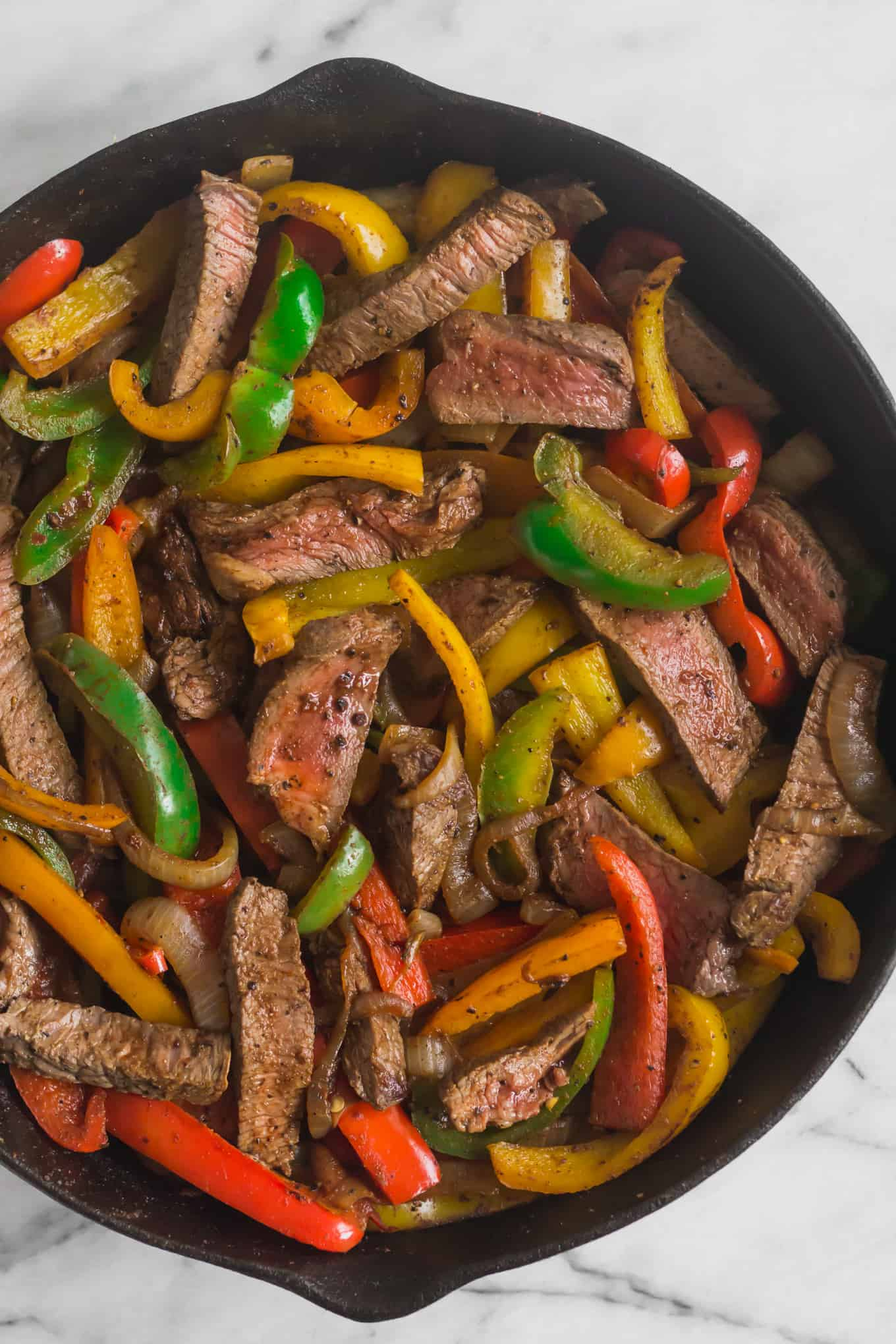 Large cast iron pan filled with steak fajitas on a white marble countertop