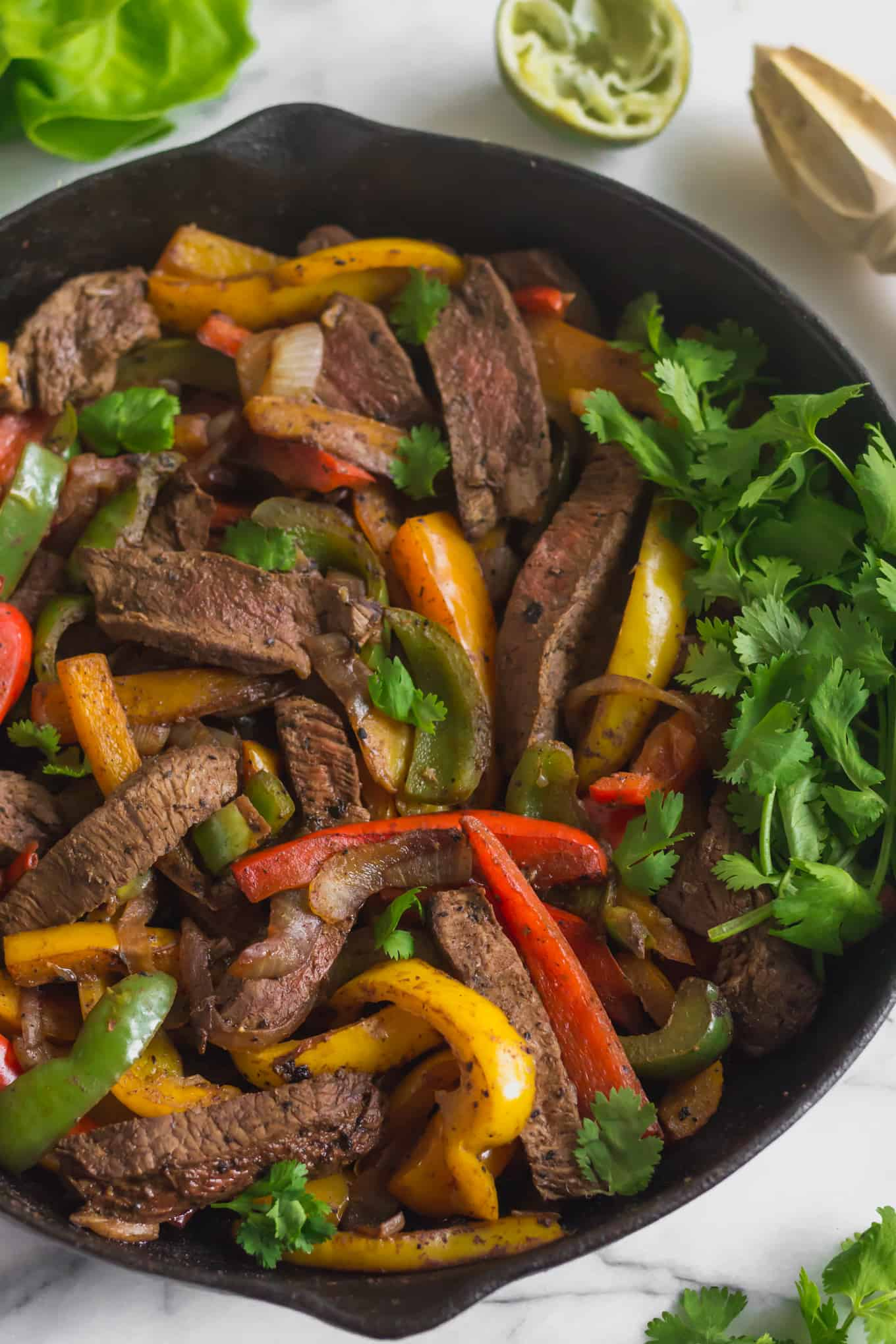 Large cast iron pan filled with steak fajitas and a handful of cilantro on a white marble countertop