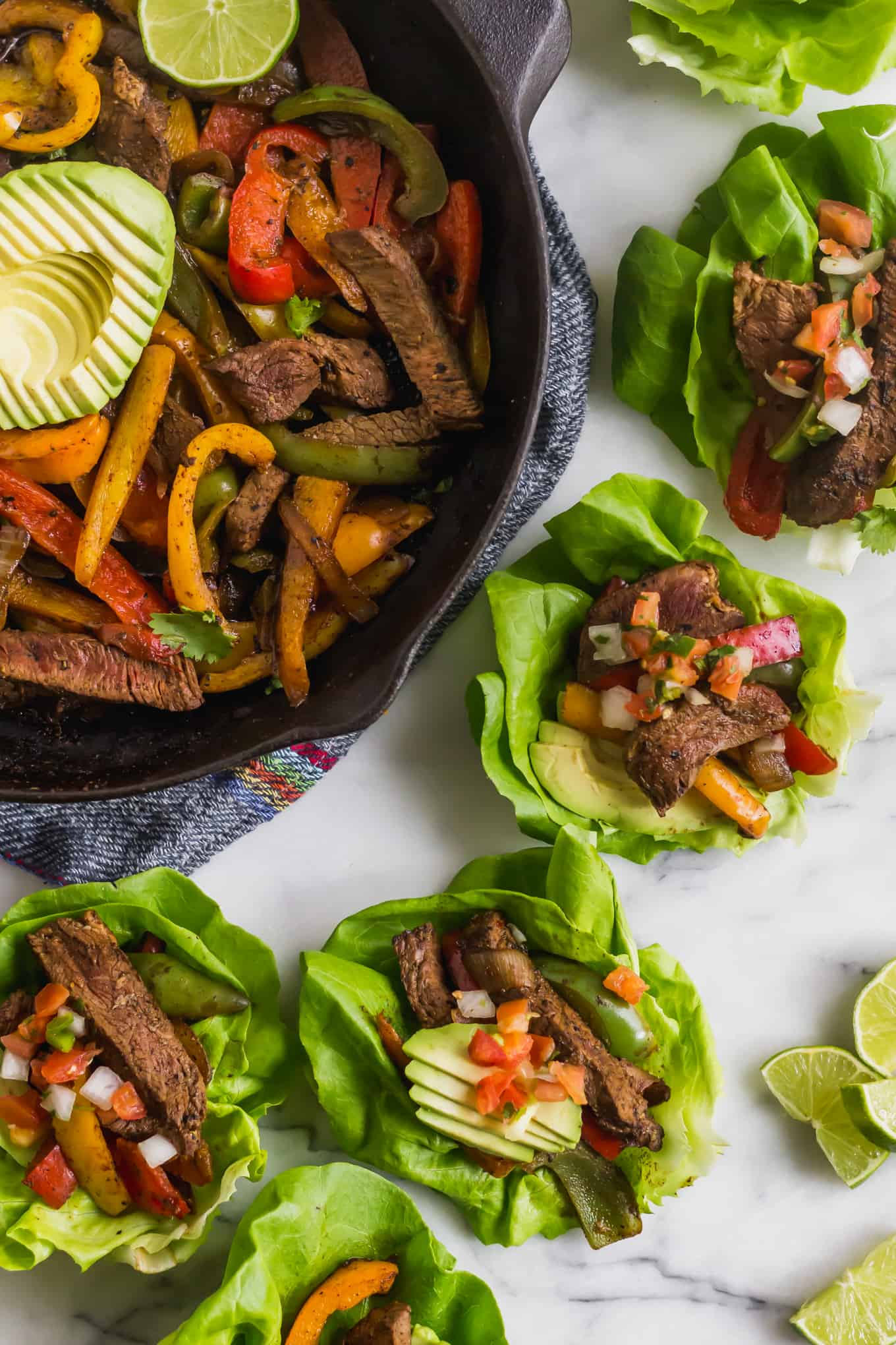Large cast iron panned filled with steak fajitas and avocado, surrounded by a bunch of steak fajita lettuce wraps and cut limes on a white countertop