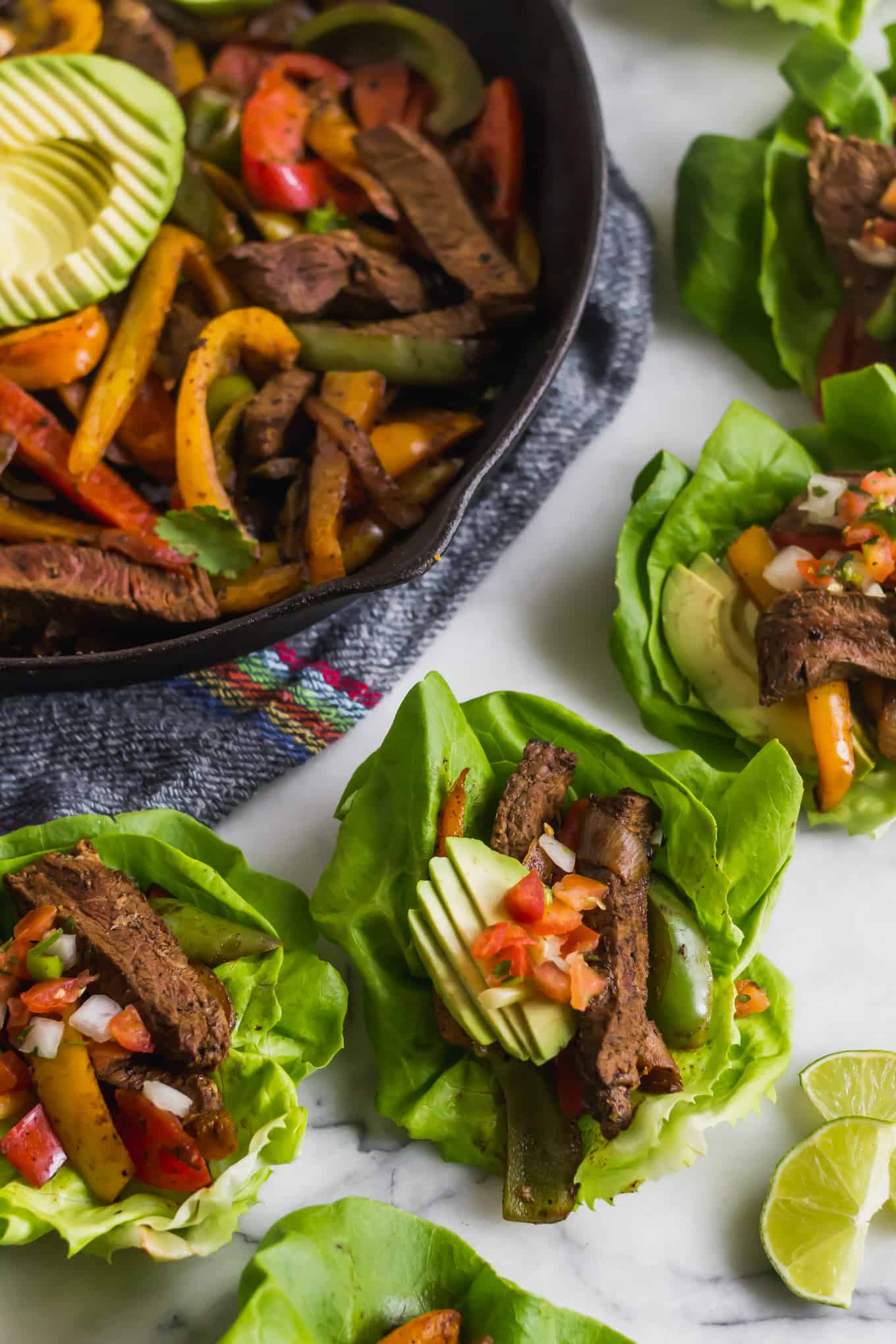 Cast iron pan filled with steak fajitas and avocado surrounded by steak fajita lettuce wraps