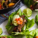 Lettuce cup filled with steak fajitas topped with avocado and pico de gallo