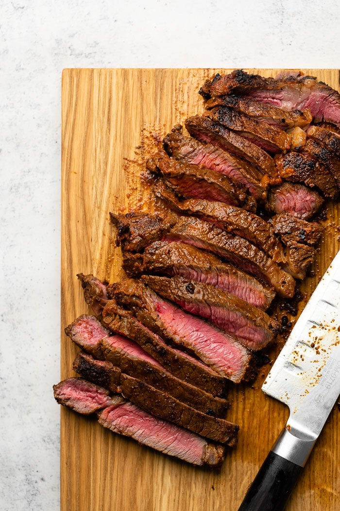 A cutting board with sliced steak on it and a knife.