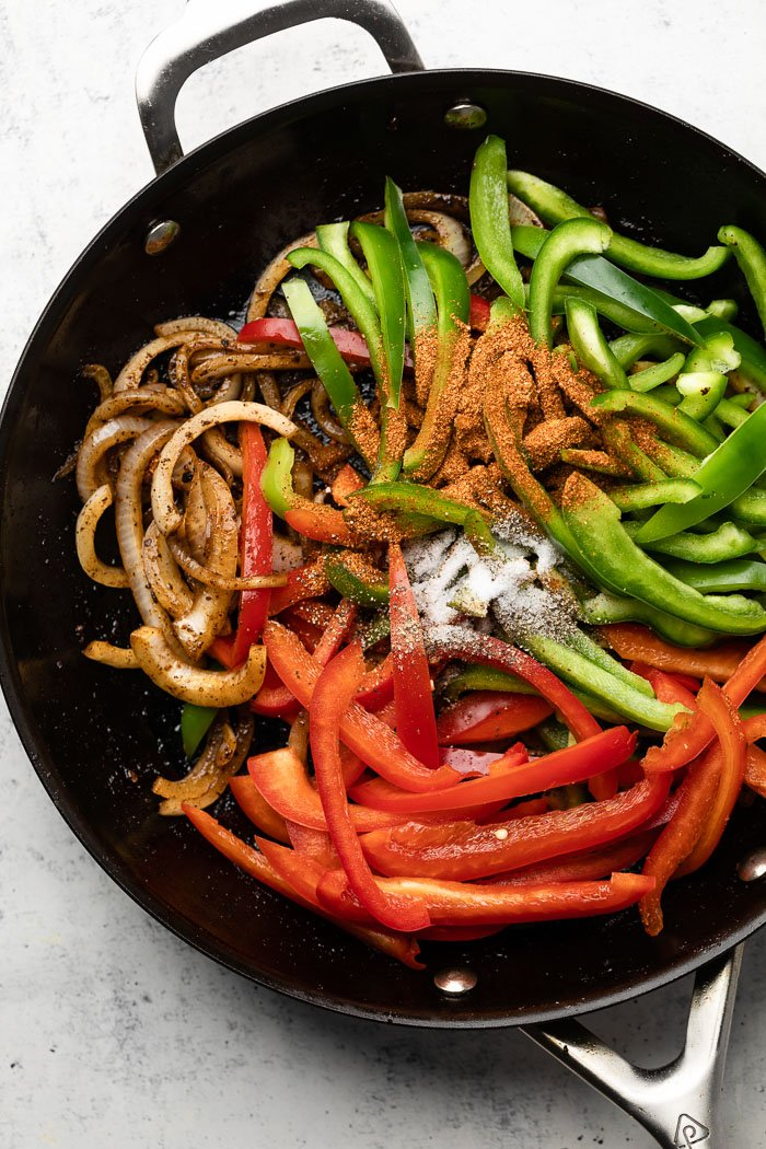 Large pan with cooked onion, raw julienned peppers, and seasonings.